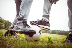 Amis jouant le football en parc Photos libres de droits