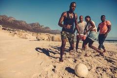 Amis jouant le football sur la plage Image libre de droits