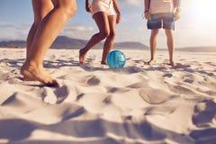 Amis jouant le football sur la plage Photographie stock libre de droits