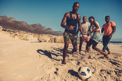 Amis jouant le football sur la plage Photos stock