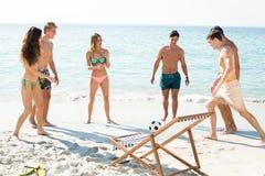 Amis jouant le football sur le rivage à la plage Image stock