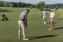 Amis jouant le golf ensemble sur le vert à la journée Photographie stock libre de droits