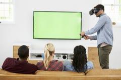 Amis jouant le jeu d'ordinateur avec le casque de réalité virtuelle Image stock