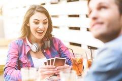 Amis jouant le jeu de carte tout en se reposant au café extérieur Images stock