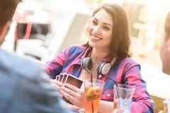 Amis jouant le jeu de carte tout en se reposant au café extérieur Images libres de droits