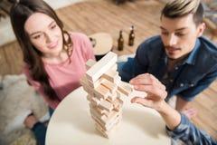 Amis jouant le jeu de jenga à la maison Photographie stock