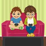 Amis jouant le jeu vidéo à la maison se reposant sur le sofa Images stock
