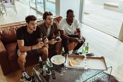 Amis jouant le jeu vidéo se reposant à la maison Photographie stock libre de droits