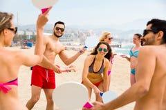 Amis jouant le matkot sur une plage Photo stock