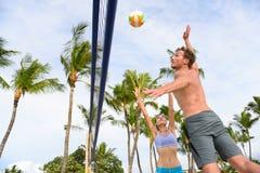 Amis jouant le sport de volleyball de plage en été Image libre de droits