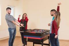 Amis jouant le Tableau du football - Foosball Images stock