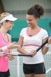 Amis jouant le tennis sur le court de tennis dehors Image libre de droits