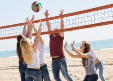 Amis jouant le volleyball à la plage Photographie stock libre de droits