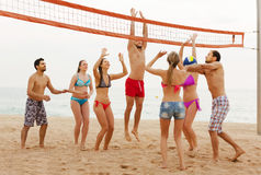 Amis jouant le volleyball à la plage Photographie stock libre de droits