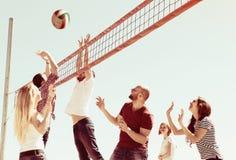 Amis jouant le volleyball à la plage Photos stock