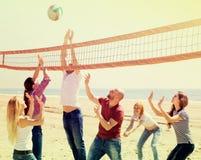 Amis jouant le volleyball à la plage Photo stock