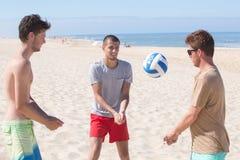 Amis jouant le volleyball de plage à la plage Image libre de droits