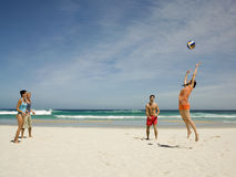 Amis jouant le volleyball sur la plage Photo stock