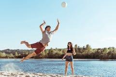 Amis jouant le volleyball sur la plage sablonneuse à la journée Photos libres de droits