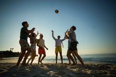 Amis jouant le volleyball sur le rivage à la plage Images libres de droits