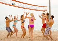 Amis jouant le volleyball sur une plage Images libres de droits