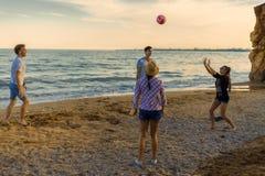 Amis jouant le volleyball sur une plage sauvage pendant le coucher du soleil Photographie stock