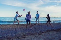 Amis jouant le volleyball sur une plage sauvage pendant le coucher du soleil Photos stock