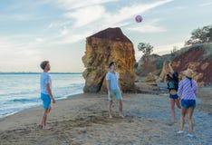 Amis jouant le volleyball sur une plage sauvage pendant le coucher du soleil Image libre de droits