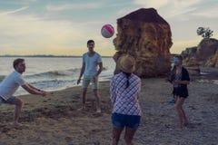 Amis jouant le volleyball sur une plage sauvage pendant le coucher du soleil Photo stock