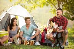 Amis jouant les tambours et la tente avant de guitare Images stock