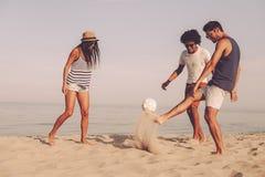 Amis jouant sur la plage Photo libre de droits