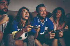 Amis jouant un jeu vidéo du football Images libres de droits