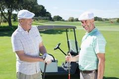 Amis jouants au golf causant près de leur boguet Photographie stock