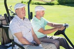 Amis jouants au golf conduisant dans leur boguet de golf Photo libre de droits