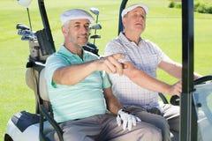Amis jouants au golf conduisant dans leur boguet de golf Image stock