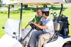Amis jouants au golf conduisant dans leur boguet de golf Images libres de droits