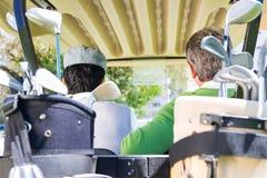 Amis jouants au golf conduisant dans leur boguet de golf Photos stock