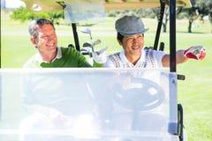 Amis jouants au golf conduisant dans leur boguet de golf Images stock