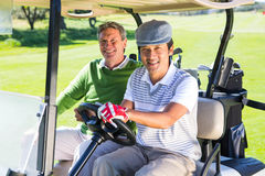 Amis jouants au golf conduisant dans leur sourire avec des erreurs de golf à l'appareil-photo Photo stock