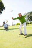Amis jouants au golf encourageant sur le putting green Images libres de droits