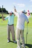 Amis jouants au golf fiving haut sur le dix-huitième trou Photos libres de droits