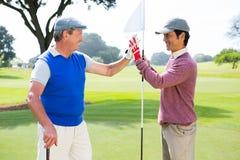 Amis jouants au golf fiving haut sur le trou Photographie stock