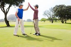 Amis jouants au golf fiving haut sur le trou Images libres de droits