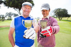 Amis jouants au golf montrant leurs tasses Photo libre de droits