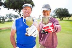 Amis jouants au golf montrant leurs tasses Image stock