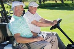 Amis jouants au golf riant ensemble dans leur boguet de golf Image libre de droits