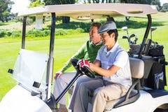 Amis jouants au golf riant ensemble dans leur boguet de golf Photographie stock libre de droits