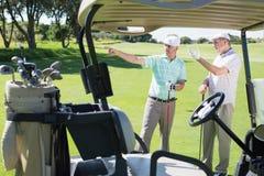 Amis jouants au golf se tenant près de leur regard avec des erreurs autour Images libres de droits