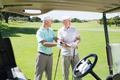 Amis jouants au golf se tenant près de leur regard avec des erreurs autour Photos libres de droits