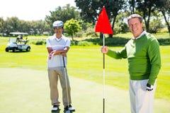 Amis jouants au golf souriant à l'appareil-photo Photos stock